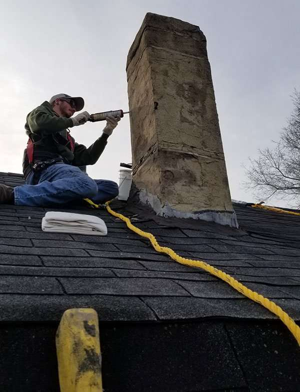 Bat exclusion by BWC worker repairing chimney mortar gaps to prevent bats from entering the exhaust flue. This chimney was then sealed and a new stainless steel chimney cap installed to prevent a bat or other animal pest from entering the home.
