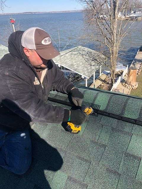 Photo of a Barnes Wildlife Control technician putting up Peak Protector on this Indian Lake home's roof.